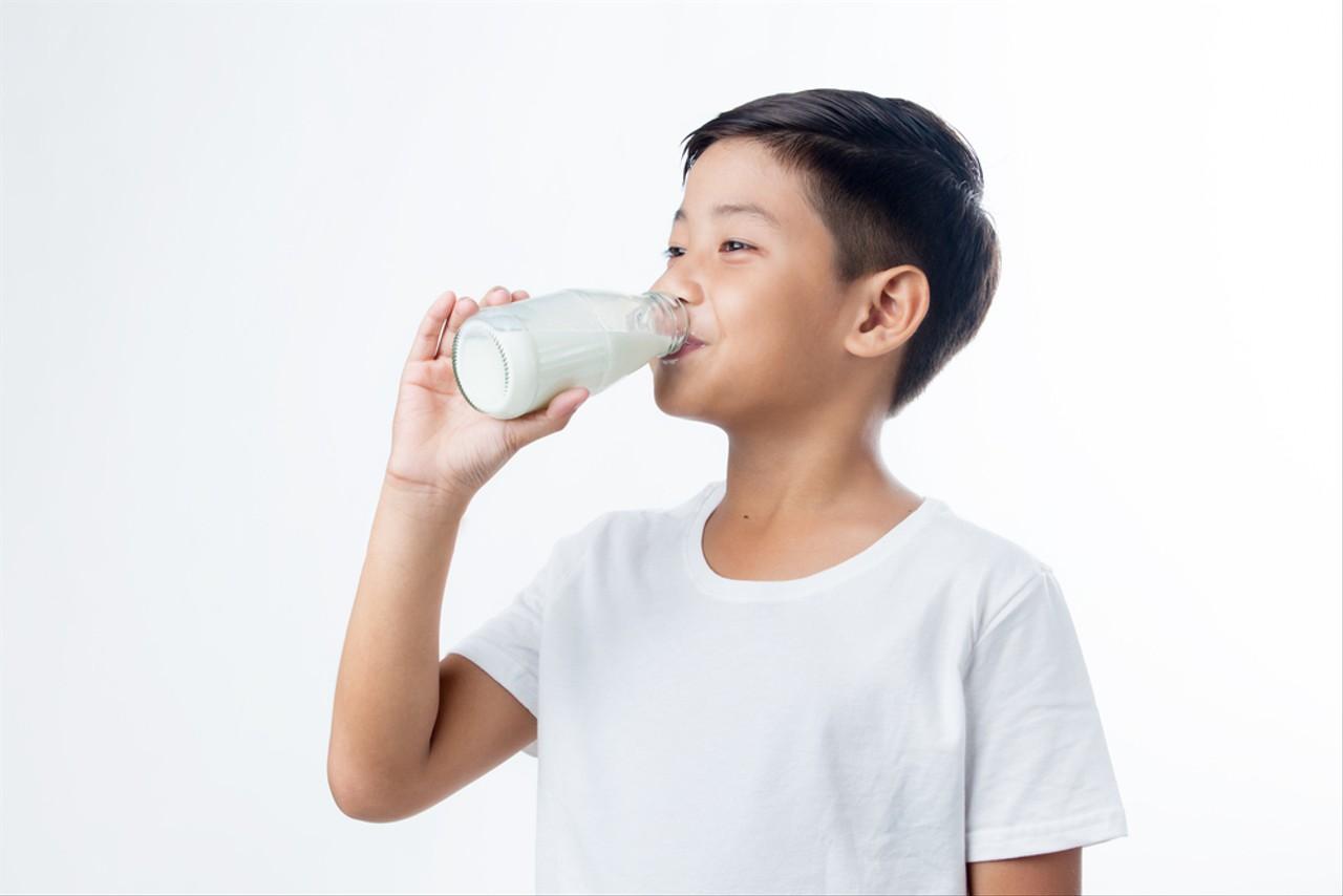 com-Ilustrasi anak minum susu.