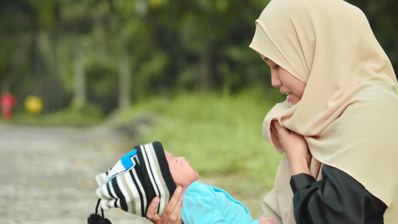 Ilustrasi ibu menyusui mengenakan hijab