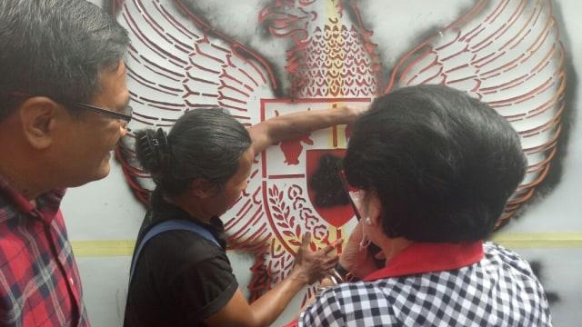Megawati menyemprotkan pilok di mural Pancasila.