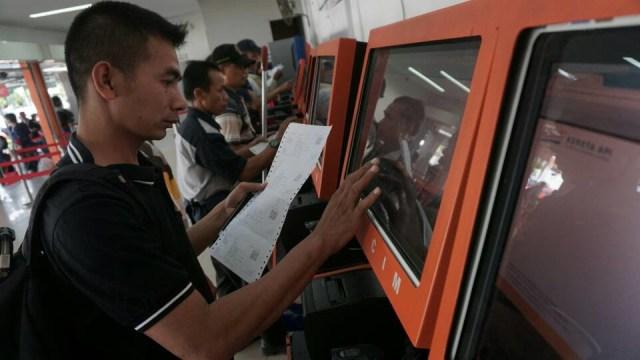Seorang penumpang mencetak tiket kereta