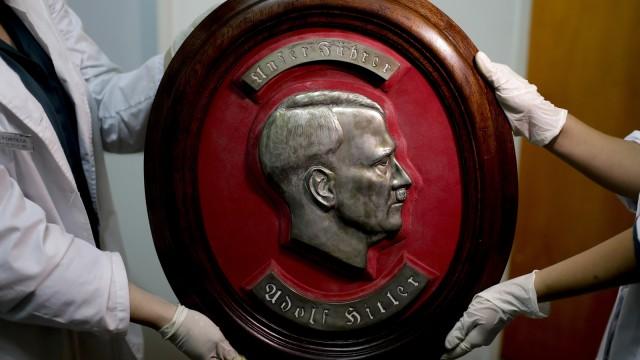 Petugas membawa patung Hitler