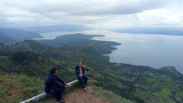 Warga menikmati pemandangan Danau Toba