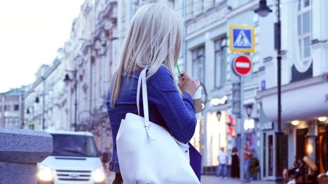 Ilustrasi perempuan membawa tas.