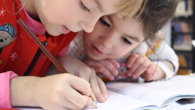 Dua orang anak yang sedang belajar