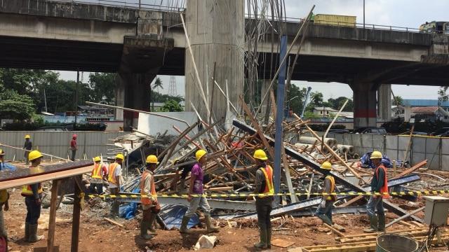 Pekerja membersihkan runtuhan timber braket