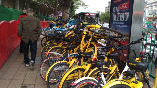 Warga melintasi tumpukan bike sharing