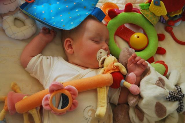 Ilustrasi Bayi Tidur dengan Mainan