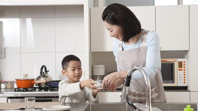 Ilustrasi anak mencuci piring.