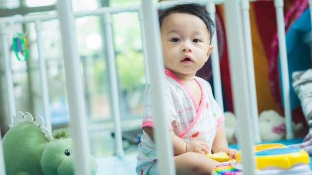 Bayi bermain di dalam pagar