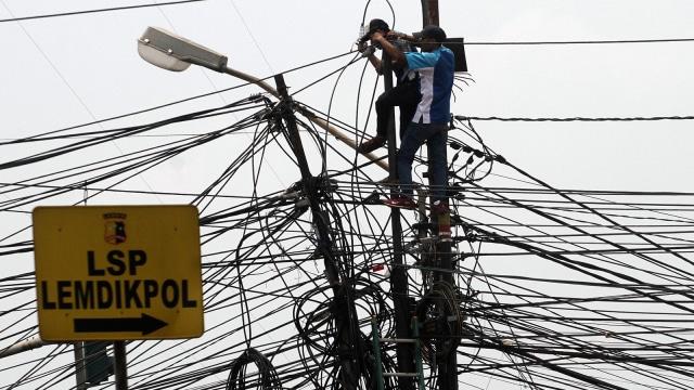 Pekerja memasang kabel telekomunikasi