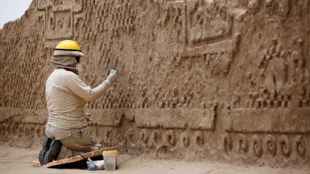 Seorang Pekerja Ahli Arkeologi Membersihkan Pahatan Dinding
