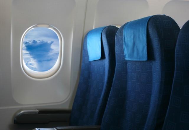 Kursi Warna Biru di Dekat Jendela Pesawat