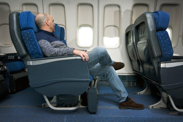 Penumpang Duduk di Kursi Pesawat Berwarna Biru