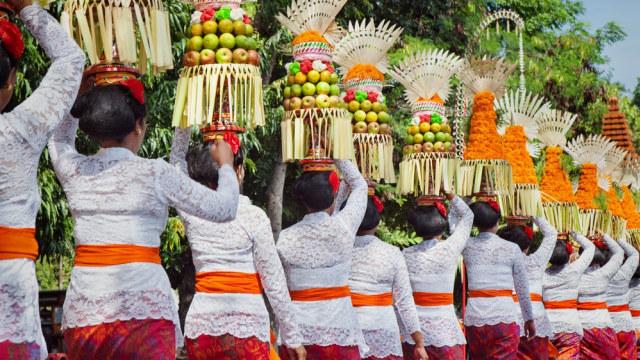 Para wanita memakai baju putih dan membawa sesajen pada Hari Raya Galungan dan Kuningan