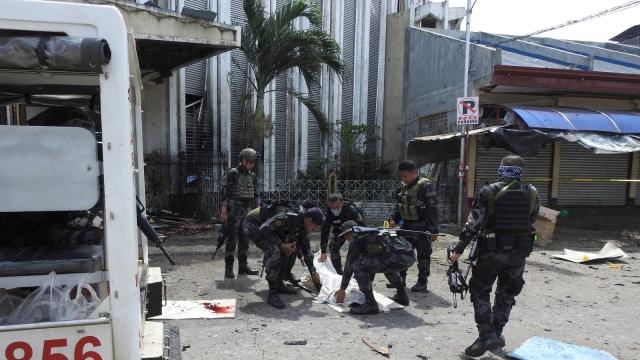 Petugas keamanan Filipina membawa kantung jenazah berisi korban ledakan di sebuah gereja di Jolo, provinsi Sulu di pulau Mindanao selatan