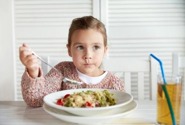 Anak perempuan mengunyah makanan secara perlahan