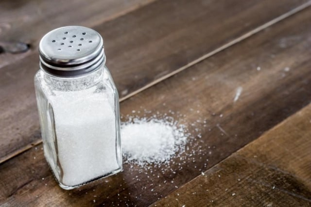 Botol garam dan tumpahan garam di meja kayu