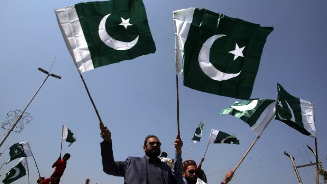 Warga membawa bendera Pakistan di tengah konflik dengan India