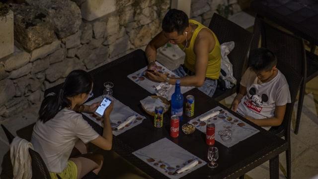 Ilustrasi main smartphone di meja makan