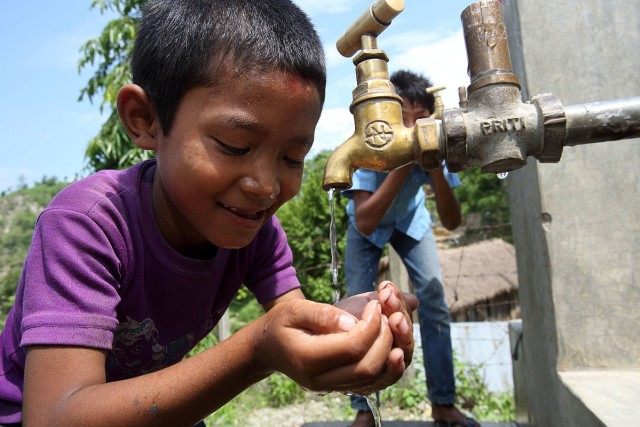 1200px-Boy_drinks_from_a_tap_at_a_NEWAH_WASH_water_project_in_Puware_Shikhar,_Udayapur_District,_Nepal._(10677936093).jpg