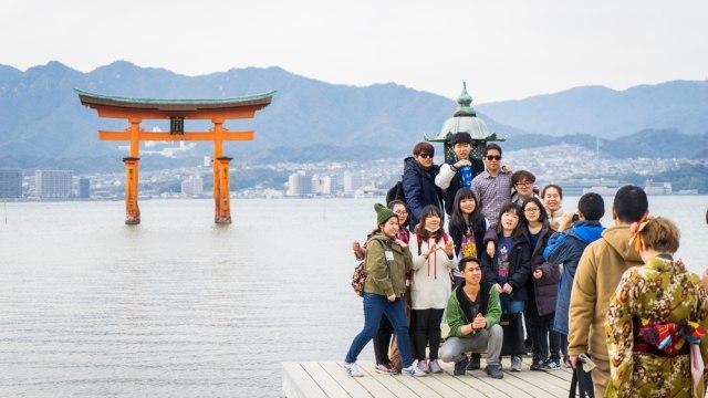 Rombongan wisatawan berfoto bersama di depan gerbang mengapung yang populer di Hiroshima
