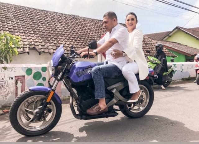 Krisdayanti naik motor usai nyoblos di TPS.