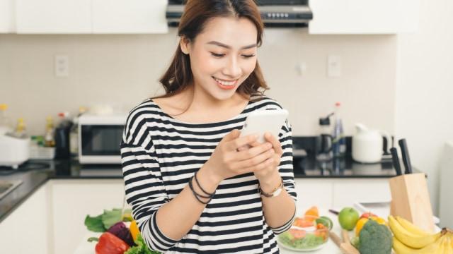 Ilustrasi wanita memegang ponsel di dapur