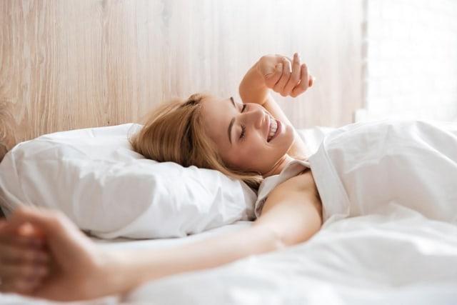 perempuan bangun dari tidur di kasur