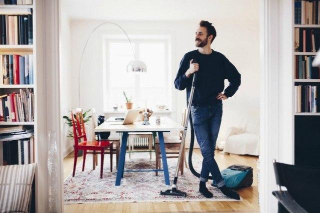 pria memegang vacuum cleaner di tengah ruangan kontemporer