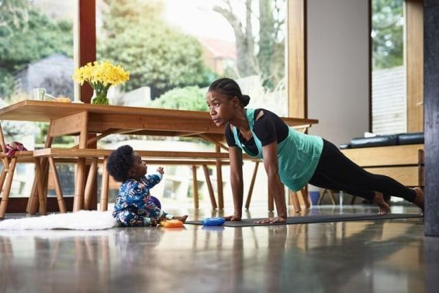 ibu olahraga di atas mat yoga dengan bayi di sampingnya dalam rumah