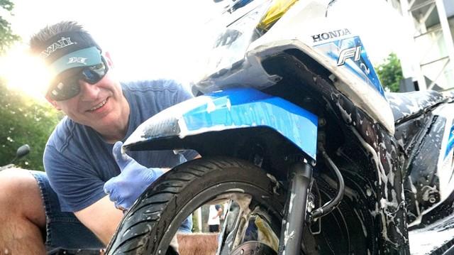 anggota Gereja Yesus Kristus memberikan pelayanan cuci motor gratis