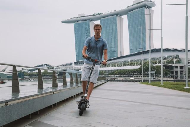 com-Mengendarai skuter di Singapura.