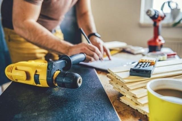 bikin rancangan untuk reparasi rumah dengan perkakas dan tumpukan kayu