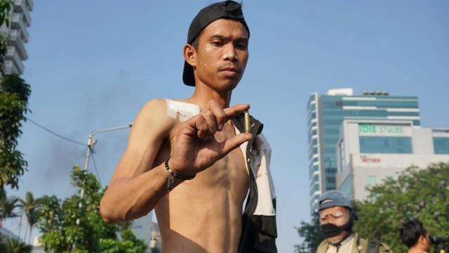 Seorang warga memperlihatkan selongsong peluru, Aksi Massa