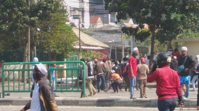 Massa bentrok dengan Kepolisian.
