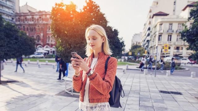 Traveler menggunakan ponsel sambil berjalan