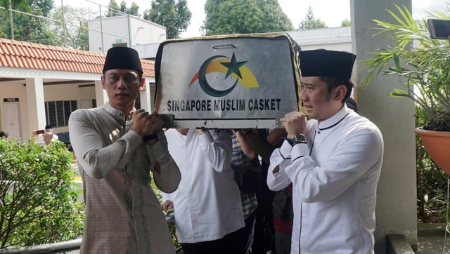 Ani Yudhoyono, Agus Harimurti  (kiri) dan Edhie Baskoro (kanan) mengangkat keranda jenazah Ani Yudhoyono yang telah tiba di Masjid Istiqamah, KBRI Singapura