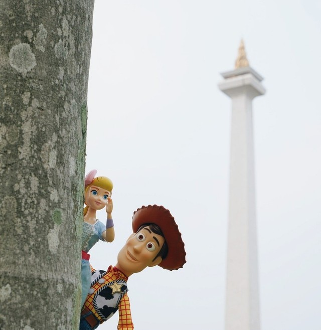 Woody dan Bo Peep bersembunyi di belakang pohon di sekitar Monas