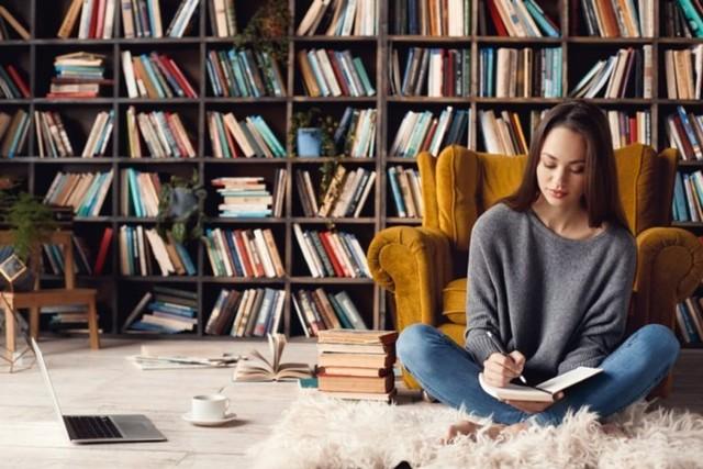 perempuan kerja dari rumah menulis di buku