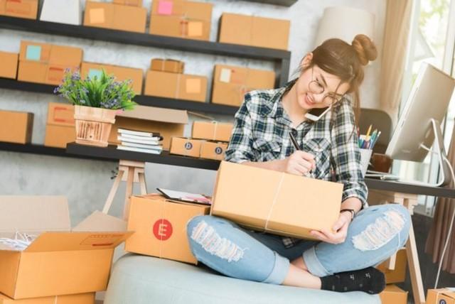 perempuan kerja dari rumah menjadi wirausaha menelepon dan mengepak barang