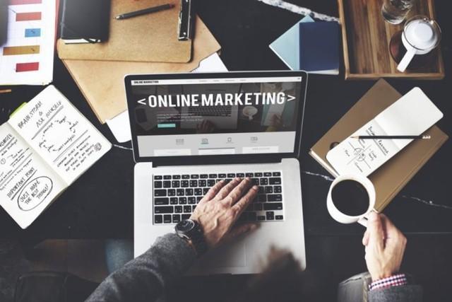 kerja dari rumah di laptop menjadi marketing online dan memegang cangkir kopi