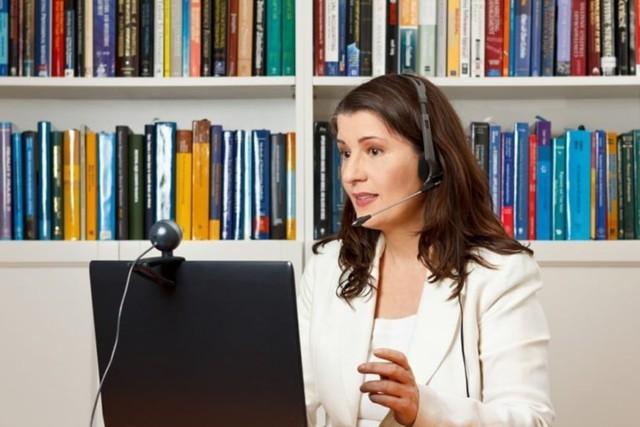 perempuan kerja dari rumah dengan laptop dan webcam menjadi guru online