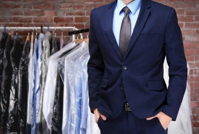 pria memakai jas dengan pakaian dry cleaning digantung