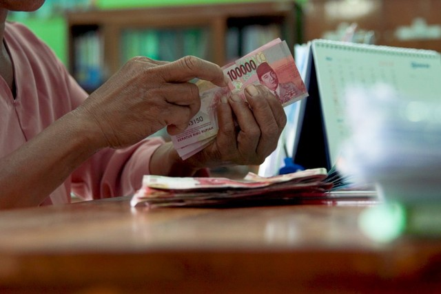Salah seorang warga Desa Bejiharjo tengah menghitung uang pinjaman dari BUMDes Maju Mandiri