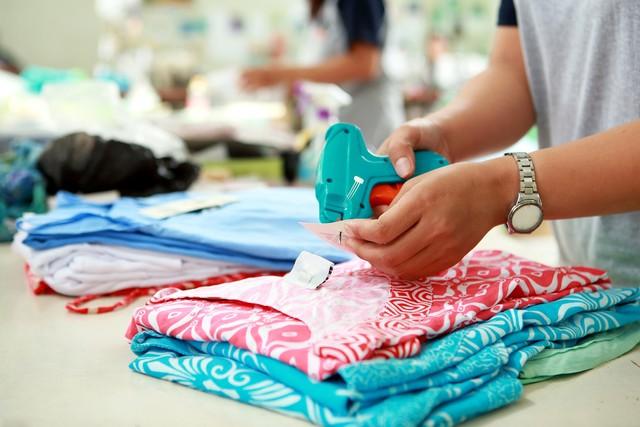 com-Ilustrasi pekerja memasang label pada produk baju. Hanya dengan menguasai pasar dalam negeri, industri TPT lokal dapat meningkatkan nilai ekspornya.