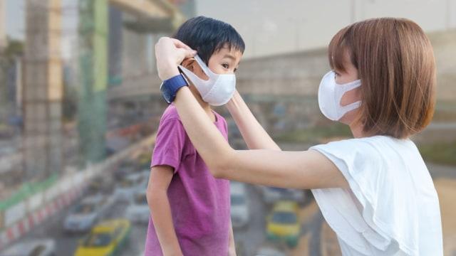 Anak dan ibu gunakan masker untuk lindungi diri dari polusi udara.
