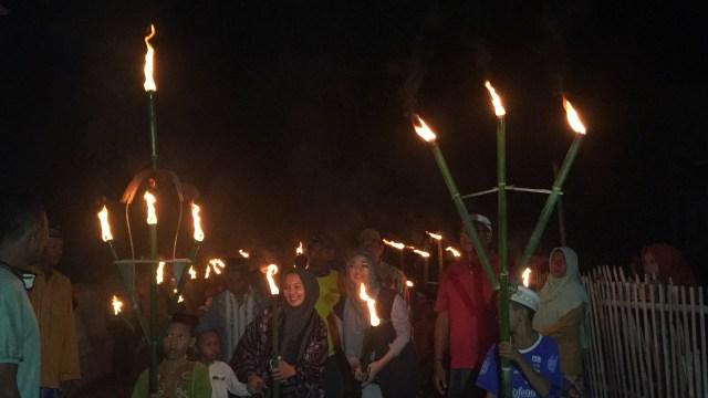 Chiki Fauzi seorang spokeperson Wardah Beautysaat mengikuti pawai obor di desa Ronting, Nusa Tenggara Timur