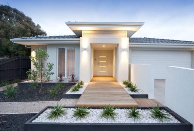 taman depan rumah sederhana dengan batu koral warna putih di taman kering