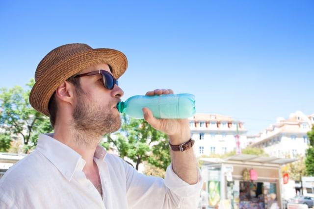Ilustrasi traveler tengah minum air putih