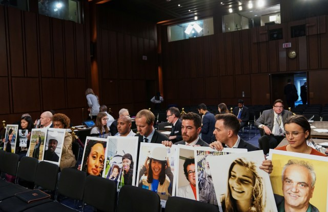 Anggota keluarga memegang foto-foto korban kecelakaan Boeing 737 MAX, CEO Boeing Dennis Muilenburg